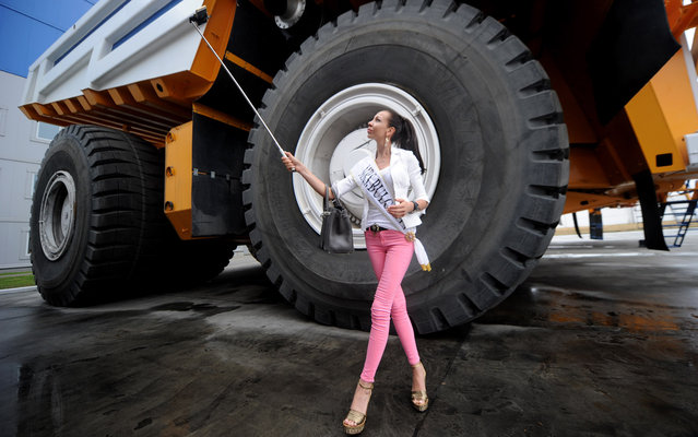"""A participant of the """"Mrs Universe 2015"""" contest takes a selfie picture as she stands close to a 360 ton payload BelAZ mining dump truck at the BelAZ plant in Zhodino, outside Minsk, on August 26, 2015. (Photo by Sergei Gapon/AFP Photo)"""