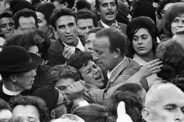 A man tries to calm a woman in summer heat and the crushing crowds in St. Peter's Square, June 6, 1963, shortly before Pope John XXIII's body was carried out so the public night pay a final tribute. (Photo by AP Photo)
