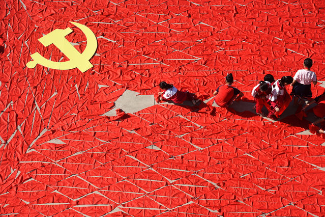 Students use red scarves to make a flag of the Communist Party of China, ahead of the 19th National Congress of the Communist Party, at a primary school in Linyi, Shandong province, China September 13, 2017. (Photo by Reuters/China Stringer Network)