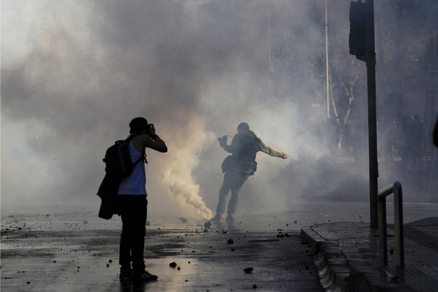 A photographer kicks a tear gas canister during a rally at Santiago city, June 23, 2011. (Photo by Ivan Alvarado/Reuters)