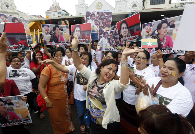 Myanmar citizens hold placards and dance as they attend a public gathering held to listen to the live speech made by Myanmar State Counselor Aung San Suu Kyi in front of City Hall in Yangon, Myanmar, 19 September 2017. Suu Kyi used the speech to address national reconcilliation and peace efforts in Myanmar in the 18 months that the nation has been under civilian rule. The Myanmar military has been under increased international scrutiny due to the refugee crisis in Bangladesh caused by ethnic Rohingya fleeing violence in Myanmar's Rakhine state due to a security crackdown. Authorities estimate that over 400,000 Rohingya have fled the violence in Rakhine State. (Photo by Nyein Chan Naing/EPA/EFE)