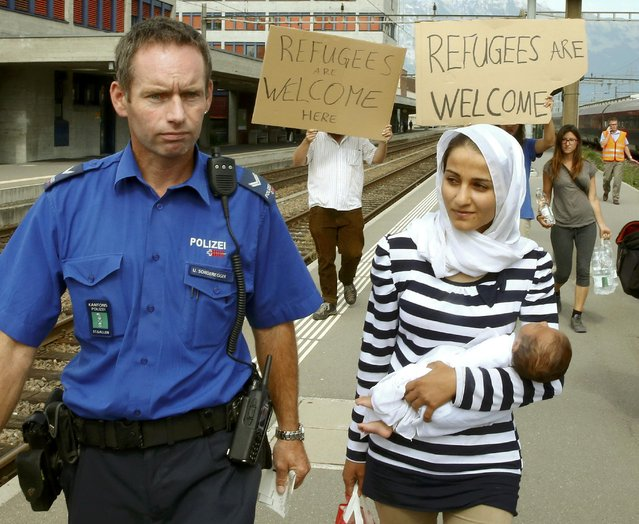A Swiss police officer accompanies a migrant from Syria carrying her baby, upon her arrival at the railway station in the north-eastern Swiss town of Buchs September 1, 2015. (Photo by Arnd Wiegmann/Reuters)