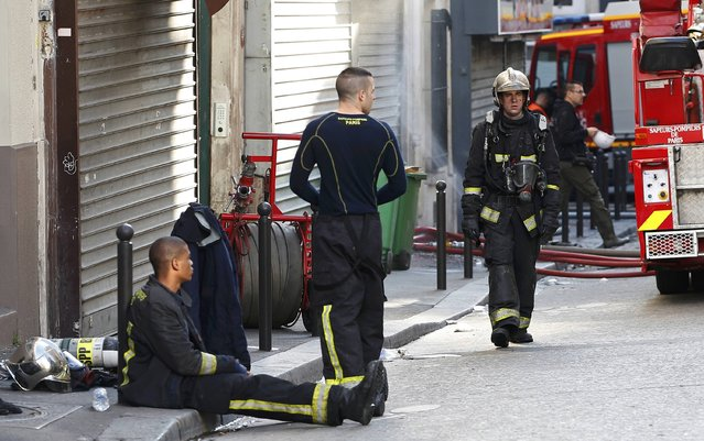 French firefighters of Paris Fire Brigade (BSPP) recover after extinguishing the fire that broke-out overnight in an apartment building in central Paris, France, September 2, 2015. The fire killed eight people on, among them two children according to official sources. Four people were also injured in the fire whose cause remains unknown. (Photo by Charles Platiau/Reuters)