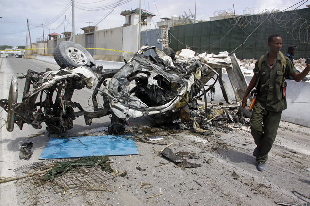 Somali soldier stand near the wreckage of a car bomb outside the UN's office in Mogadishu, Somalia, Tuesday, July 26, 2016. A suicide bomber detonated an explosives-laden car outside the United Nations Mine Action Service offices in Mogadishu, killing 13 people, including seven U.N. guards, a Somali police official said. (Photo by Farah Abdi Warsameh/AP Photo)