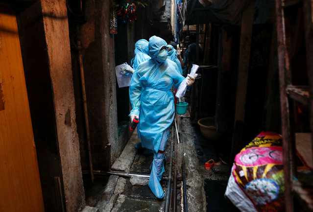 Healthcare workers enter a resedential area to check residents during a nationwide lockdown to slow the spreading of the coronavirus disease (COVID-19), in Mumbai, India, April 20, 2020. (Photo by Francis Mascarenhas/Reuters)