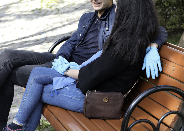 A couple wear protective gloves as they sit together in a public garden amid the coronavirus outbreak, in Ankara, Turkey Thursday, March 26, 2020. (Photo by Burhan Ozbilici/AP Photo)