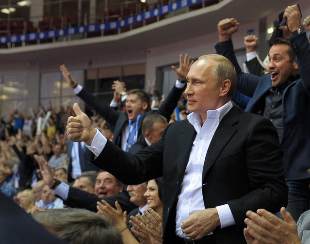 Russian President Vladimir Putin, foreground right, gestures, as he attends the Judo World Cup in the city of Chelyabinsk in Siberia, Russia, on Sunday, August 31, 2014. Putin is calling on Ukraine to immediately start talks on a political solution to the crisis in eastern Ukraine, including discussing statehood. (Photo by Alexei Druzhinin/AP Photo/RIA Novosti/Presidential Press Service)