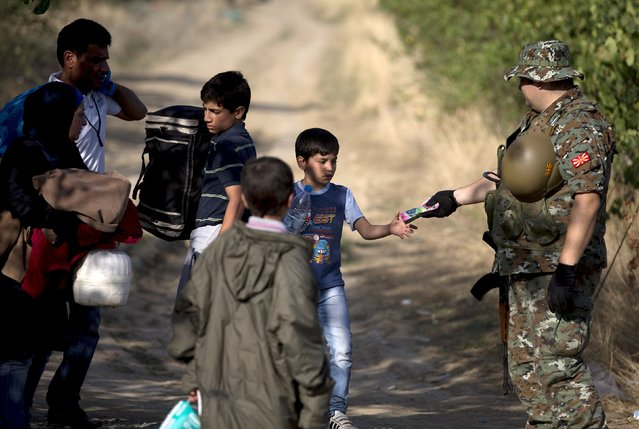 A migrant boy receives a pack of juice from a Macedonian soldier after crossing the Macedonian-Greek border near Gevgelija, Macedonia, September 5, 2015. (Photo by Stoyan Nenov/Reuters)
