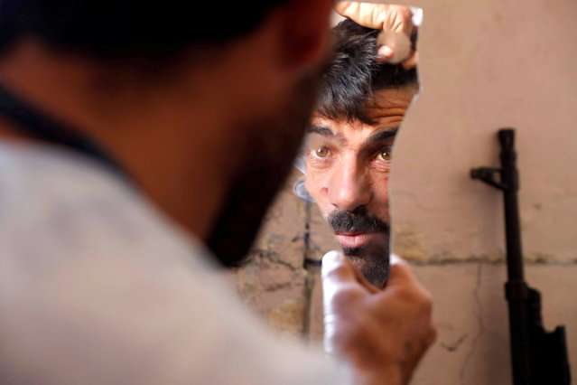 A fighter of Syrian Democratic Forces fixes his hair using a broken mirror at the frontline in Raqqa, Syria October 6, 2017. Picture taken October 6, 2017. (Photo by Erik De Castro/Reuters)
