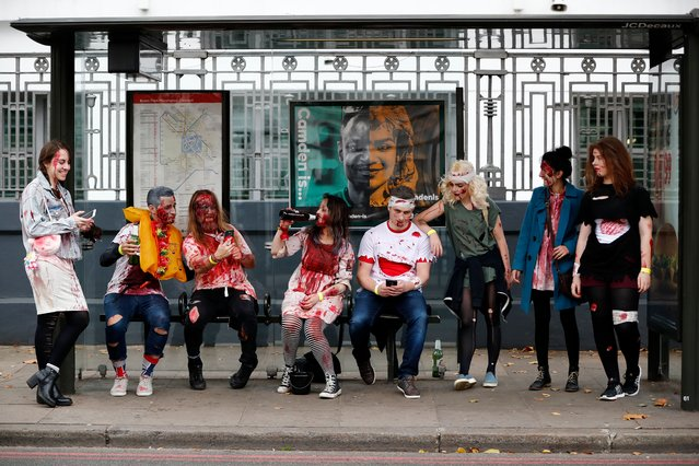 """People wearing costumes gather at a bus stop before participating in a """"Zombie Walk"""" on World Zombie Day, in London on October 7, 2017. (Photo by Tolga Akmen/AFP Photo)"""
