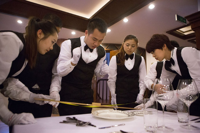 Students work together to set a formal dinner using rulers and tape measures at The International Butler Academy China on September 16, 2014 in Chengdu, China. (Photo by Taylor Weidman/Getty Images)