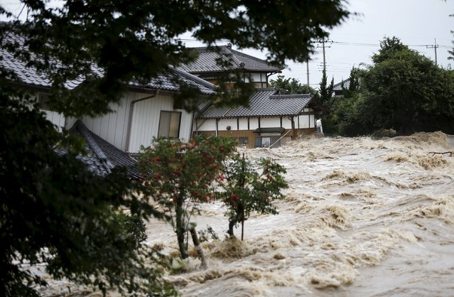 Houses are pictured amid flood waters at a residential area inundated by the Kinugawa river, caused by typhoon Etau, in Joso, Ibaraki prefecture, Japan, September 10, 2015. (Photo by Issei Kato/Reuters)