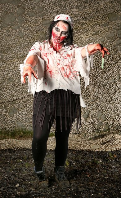 A visitor to the Shocktober Fest dressed as a zombie poses on October 6, 2012 in Turners Hill, England. People dressed as zombies from around the United Kingdom have converged on Tulleys Farm in an attempt to set a new Guinness World Record for the most zombies together in one place.  (Photo by Peter Macdiarmid)