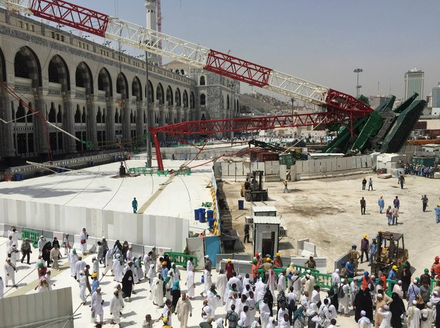 Muslim pilgrims walk near a construction crane which crashed in the Grand Mosque in the Muslim holy city of Mecca, Saudi Arabia September 12, 2015. (Photo by Mohamed Al Hwaity/Reuters)