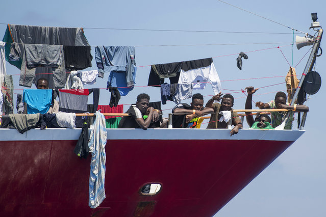 Migrants dry their clothes aboard a tourist boats some 20 kilometers from Malta, Tuesday, June 2, 2020. More than 400 migrants are living aboard pleasure cruise vessels, bobbing in the sea off Malta, many of them for weeks now. Rescued from human traffickers' unseaworthy boats in several operations in the central Mediterranean since late April, the migrants, along with the Maltese government, are waiting for European Union countries to offer to take them. (Photo by Rene' Rossignaud/AP Photo)