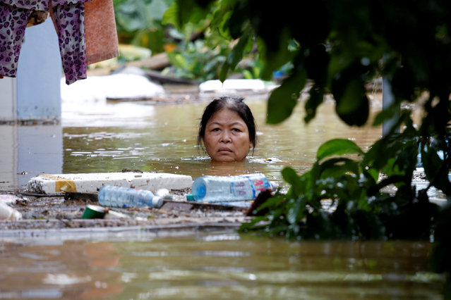 A woman wades through a submerged street at the UNESCO heritage ancient town of Hoi An after typhoon Damrey hits Vietnam November 6, 2017. (Photo by Reuters/Kham)