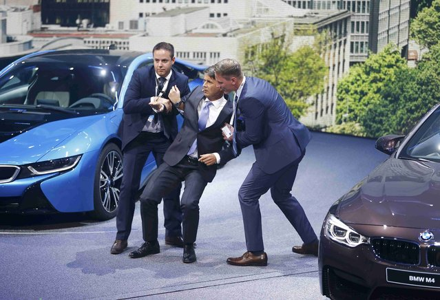 BMW CEO Harald Krueger (C) is helped after he collapsed at a presentation during the media day at the Frankfurt Motor Show (IAA) in Frankfurt, Germany, September 15, 2015. (Photo by Kai Pfaffenbach/Reuters)