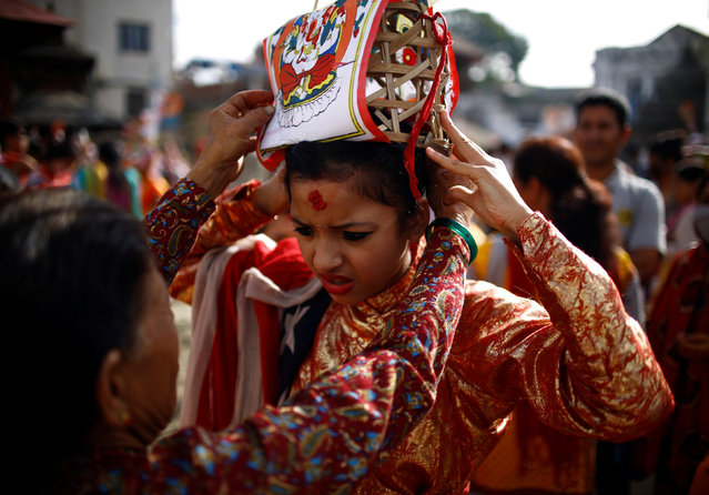 "A girl is dressed up to participate in a parade to mark the Gaijatra festival, also known as ""cow festival"", in Kathmandu, Nepal, August 19, 2016. Hindus in Kathmandu celebrate the festival to ask for salvation and peace for their departed loved ones. Cows are regarded as holy animals in Nepal which help departed souls to reach heaven. (Photo by Navesh Chitrakar/Reuters)"