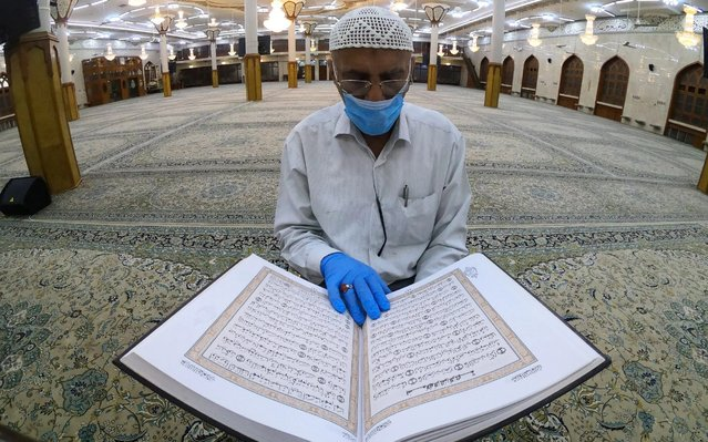 Abdul Hussein Mohammed Hassan, the muezzin of the Basra Al-Musawi mosque, one of the city's larger mosques, reads the Koran alone since all places of worship remain closed as part of the preventive measures against the spread of the coronavirus disease (COVID-19), in Basra, Iraq on May 2, 2020. (Photo by Mohammed Aty/Reuters)