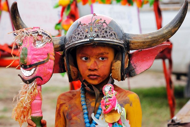 A boy wearing a horned helmet and body paint arrives for Chonburi's annual buffalo race festival, east of Bangkok, October 7, 2014. (Photo by Chaiwat Subprasom/Reuters)