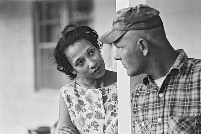 """Mildred and Richard Loving, pictured on their front porch in King and Queen County, Virginia, in 1965. In June 1958, the couple went to Washington DC to marry, to work around Virginia's Racial Integrity Act of 1924, which made marriage between whites and non-whites a crime. After an anonymous tip, police officers raided their home a month later, telling the Lovings their marriage certificate was invalid. In 1959, the Lovings pled guilty to """"cohabiting as man and wife, against the peace and dignity of the Commonwealth"""". (Photo by Grey Villet/The Guardian)"""