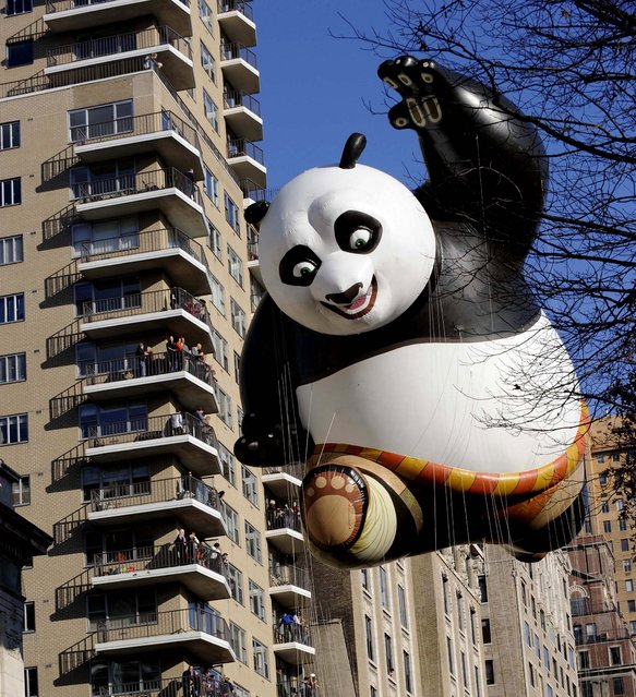 The Kung Fu Panda balloon passes an apartment building on New York's Central Park West during the 86th annual Macy's Thanksgiving Day Parade. (Photo by Louis Lanzano/Associated Press)