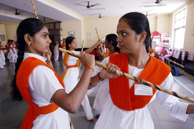 A woman activist of the Vishwa Hindu Parishad or World Hindu Council, a hardline Hindu organisation, train in the art of fighting with sticksduring a summer training camp, in Bombay May 17, 2003. (Photo by Sherwin Crasto/Reuters)