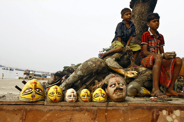 Boys sit next to clay idols of the Hindu goddesses and a demon after idols of Durga were immersed into the Ganges river in Kolkata October 3, 2014. (Photo by Rupak De Chowdhuri/Reuters)