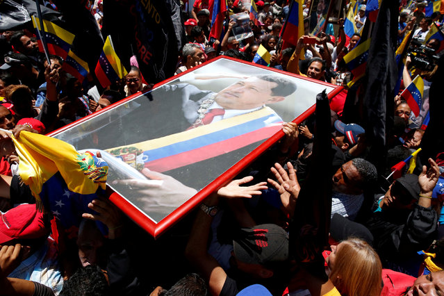 """Supporters of Venezuela's President Nicolas Maduro demonstrate outside Palacio Federal Legislativo with a picture of Venezuela's late President Hugo Chavez during the National Constituent Assembly's first session, in Caracas, Venezuela, August 4, 2017. Carlos Garcia Rawlins: """"After winning a majority in the National Assembly in 2015, lawmakers of the opposition removed all images of the late President Hugo Chavez from the main building and gardens. This act was seen by Chavez's supporters as a huge offence and they promised that someday he would be returned and honoured again. As soon as the Government won the National Constituent Assembly election, the very day of the installation ceremony, elected members and their supporters gathered outside the building and brought images of Chavez back"""". (Photo by Carlos Garcia Rawlins/Reuters)"""