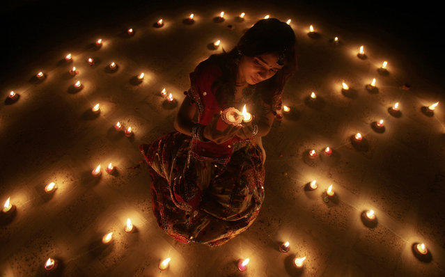 A woman lights an earthen lamp during the celebrations on the eve of the Hindu festival of Diwali in Ahmedabad October 16, 2009. (Photo by Amit Dave/Reuters)