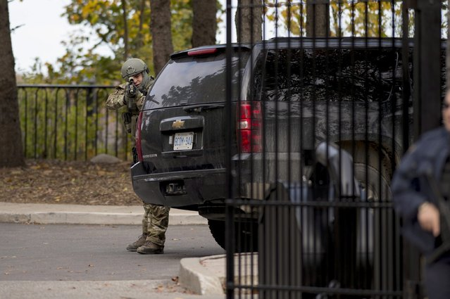 A heavily armed RCMP officer takes position at the gate of 24 Sussex Dr., the official residence of the Prime Minister, on Wednesday, October 22, 2014. (Photo by Justin Tang/AP Photo/The Canadian Press)