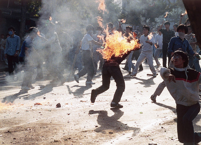 A South Korean student engulfed in flames runs for safety as his compatriots launch home-made firebombs toward riot police during anti-government, anti-Olympic demonstrations at Korea University in Seoul, South Korea on September 29, 1988. (Photo by AP Photo)