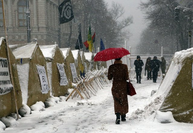 Under heavy snowfall a woman passes by a tent camp placed by supporters of the Movement of New Forces, the political party led by Mikheil Saakashvili in front of the parliament building in Kiev, Ukraine, Monday, December 18, 2017. The streets around Parliament have been the scene of recent protests demanding the resignation of Ukrainian President Petro Poroshenko. (Photo by Efrem Lukatsky/AP Photo)