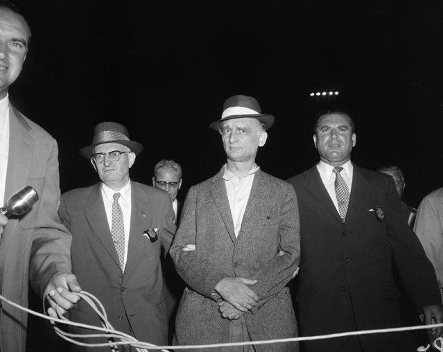 Col. Rudolf Ivanovich Abel, 55-year-old accused Soviet spy, is accompanied by U.S. Marshal, William E. Smith, left, and Joe Job, right, after arrival at Newark Airport, late August 8, 1957. Abel, a 9-year resident of Brooklyn where he posed as an artist, is charged with being a key Russian spy in the U.S. (Photo by Marty Lederhandler/AP Photo)