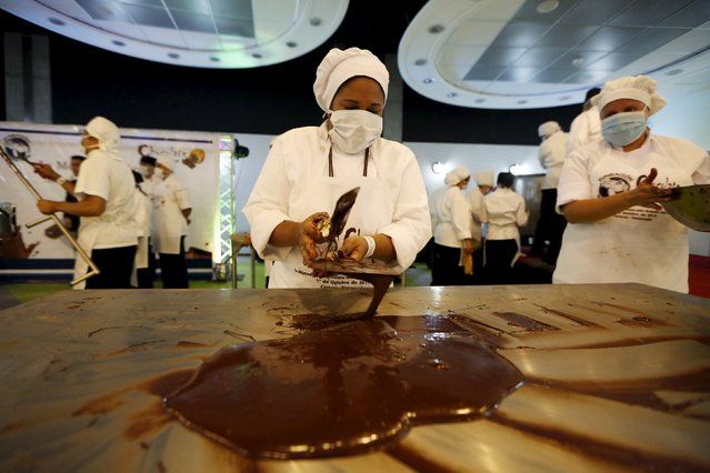 A worker spreads chocolate out on a metal table to cool it off during an attempt to break the Guinness World Record for the biggest chocolate coin in Caracas, Venezuela, October 1, 2015. (Photo by Carlos Garcia Rawlins/Reuters)