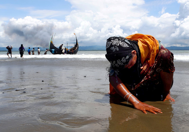 An exhausted Rohingya refugee woman touches the shore after crossing the Bangladesh-Myanmar border by boat through the Bay of Bengal, in Shah Porir Dwip, Bangladesh, September 11, 2017. (Photo by Danish Siddiqui/Reuters)
