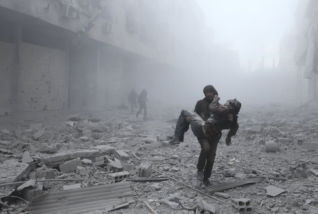 A wounded man is carried following an air strike on the rebel-held besieged town of Arbin, in the eastern Ghouta region on the outskirts of the capital Damascus on January 2, 2018. (Photo by Abdulmonam Eassa/AFP Photo)