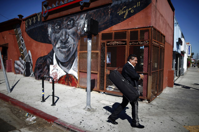 A mariachi musician walks past a mural in the Boyle Heights area of Los Angeles, home to many Mexican migrants, in California August 5, 2014. Immigration has become a hot button issue ahead of U.S. midterm elections on November 4, and despite arguments from the White House that legal migration benefits businesses, a recent opinion poll found most Americans believe migrants place a burden on the economy. (Photo by Lucy Nicholson/Reuters)