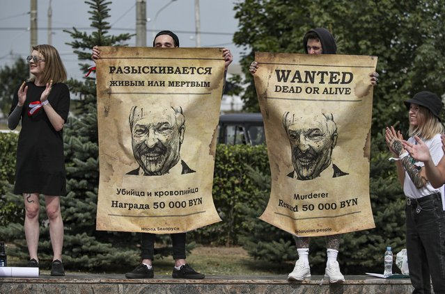 Protesters hold the posters with Belarusian President Alexander Lukashenko portraits standing near enter of the factory of refrigerators, freezers and washing machines Atlant and calling workers to join in strike and protests in Minsk, Belarus, 18 August 2020. The Belarus opposition has called for a general strike from 17 August on, a day after tens of thousands of demonstrators gathered in the capital Minsk in peaceful protest. Long-time president Lukashenko, in a defiant speech on 16 August, rejected calls to step down amid mounting pressure after unrest erupted in the country over alleged poll-rigging and police violence at protests following election results claiming that he had won a landslide victory in the 09 August elections. (Photo by Tatiana Zenkovich/EPA/EFE)