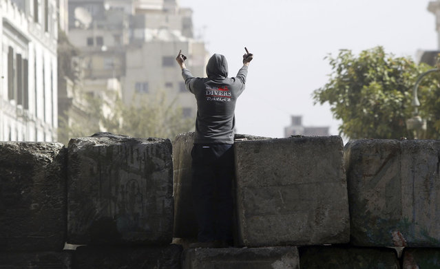 A protester on the wall towards riot police along Sheikh Rihan street near Tahrir Square in Cairo, on January 25, 2013. Opponents of Morsi and his Muslim Brotherhood allies massed in Cairo's Tahrir Square to revive the demands of a revolution they say has been betrayed by Islamists. (Photo by Amr Abdallah Dalsh/Reuters/The Atlantic)