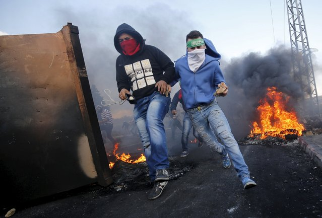 Palestinian protesters run for cover during clashes with Israeli troops near the Jewish settlement of Beit El, near the West Bank city of Ramallah October 9, 2015. (Photo by Mohamad Torokman/Reuters)