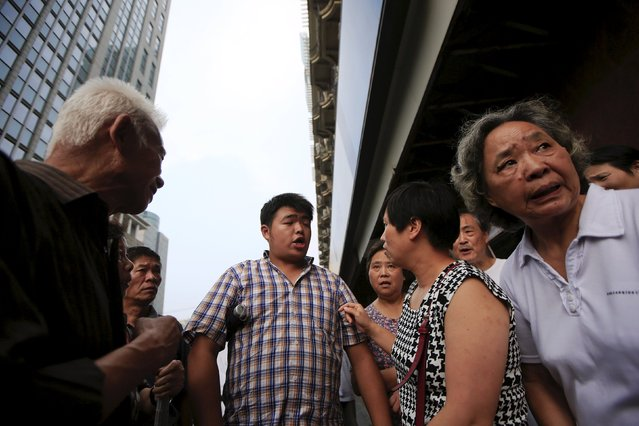 """Wang Ji, 29, recommends a stock to other investors at a """"street stock salon """" in central Shanghai, China, August 29, 2015. Wang said he has been trading stocks for about ten years. For at least a decade, an area next to the People's Square temporarily has transformed itself into a """"street stock salon"""" during weekends, with investors from all over Shanghai coming to gather stock information and learn trading skills from others. A few businessmen also make use of the occasion to promote their stock analysis software. (Photo by Aly Song/Reuters)"""