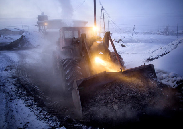 Heating for the town is provided by a coal-fired water heating plant. Every morning this digger delivers fresh coal to the plant & carries away the burnt cinder. (Photo by Amos Chapple/Courtesy Images/RFE/RL)
