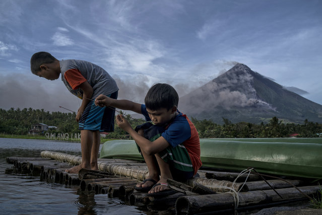 Children fish as Mayon volcano spews ash and lava on January 17, 2018 in Camalig, Albay, Philippines. (Photo by Jes Aznar/Getty Images)