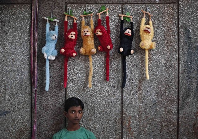 A boy selling stuffed toys waits for customers at his roadside shop in the old quarters of Delhi November 12, 2014. (Photo by Adnan Abidi/Reuters)