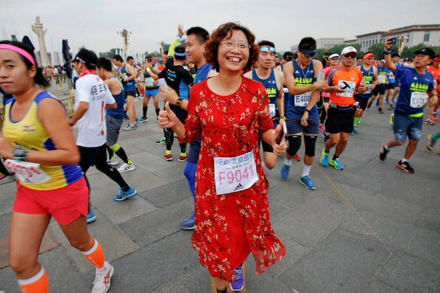 A participant wearing a traditional dress gestures while running past the Tiananmen gate during the Beijing Marathon in Beijing, China, September 17, 2016. (Photo by Damir Sagolj/Reuters)
