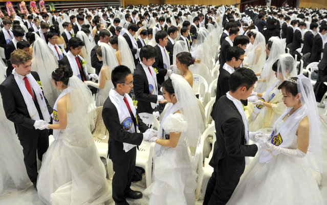 """Newly-married couples hold hands to pray during a mass wedding organised by the Unification Church and held in the church's headquarters in Gapyeong, east of Seoul, on February 17, 2013 that saw some 3,500 couples matched by the church tie the knot.  The Unification Church, set up by Sun Myung Moon in Seoul in 1954, is one of the world's most controversial religious organisations, and its devotees are often dubbed """"Moonies"""" after the founder. (Photo by Kim Jae-Hwan/AFP Photo)"""