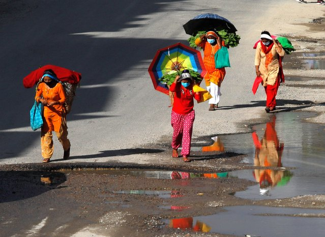 A nepalese womans carrying vegetables walking along a deserted street while wearing a face mask during lockdown imposed by the government amid concerns over the rising spread of coronavirus disease in Kathmandu, Nepal on Friday, August 28, 2020.The Kathmandu valley is under a complete lock down, in an effort to combat the spread of coronavirus and COVID-19. (Photo by Saroj Baizu/NurPhoto via Getty Images)