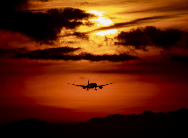 An aircraft approaches the airport in Frankfurt, Germany, as the sun rises on Thursday, August 27, 2020. With more and more tourists coming back from vacation rising numbers over Covid-19 infections are expected all over Germany. (Photo by Michael Probst/AP Photo)