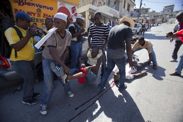 Protesters aid a man who was shot in the leg, left, and another who was shot in the neck, lying on the ground, after clashes broke out at an anti-government protest in Port-au-Prince, Haiti, Tuesday, November 18, 2014. The march began peacefully when a crowd grew to a few thousand people in slums that are opposition strongholds. (Photo by Dieu Nalio Chery/AP Photo)